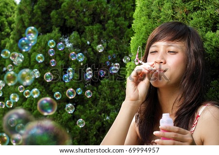beautiful young woman playing with bubble in the garden