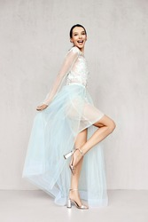 Beautiful young woman plays with hem of transparent pale tulle dresses with lace