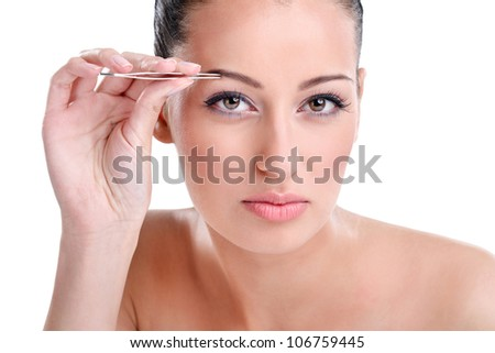 Beautiful young woman plucking eyebrows, looking at camera as mirror