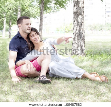 Beautiful young woman pointing at copyspace to her boyfriend in park