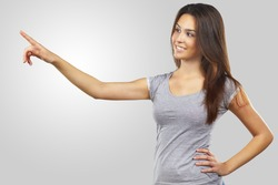 beautiful young woman pointing her finger towards blank space