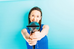 beautiful young woman pointing to the front with a professional hair dryer with blue background. hair care concept. beauty hairdresser