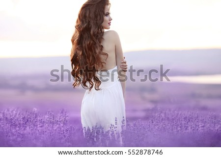Beautiful young woman portrait in lavender field. Attractive brunette girl with long curly hair style in white dress dreaming.