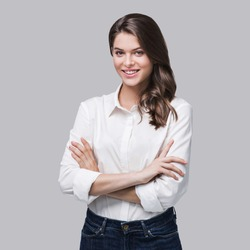 Beautiful young woman portrait. Smiling businesswoman entrepreneur with crossed arms looking at camera, isolated on gray background. People, business, student, beauty concept