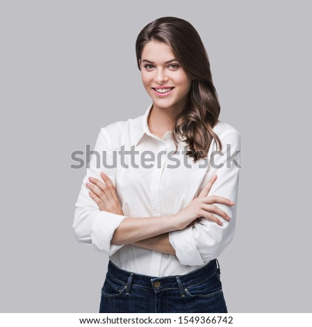Beautiful young woman portrait. Smiling businesswoman with folded arms looking at camera, isolated on gray background