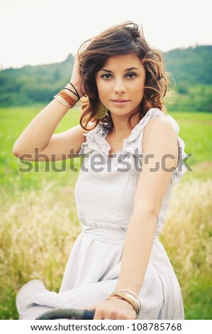 Beautiful young woman portrait with bike in a country road. - stock photo