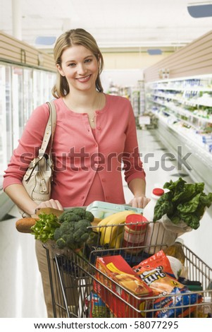Beautiful young woman poses in a grocery store with a shopping cart full of food.  Vertical shot.