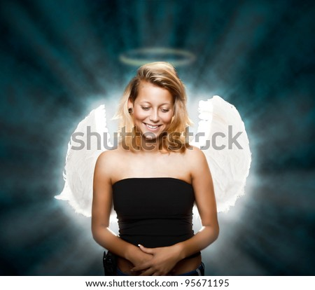 Beautiful young woman posing as innocent angel - stock photo