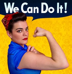 Beautiful young woman posing as working girl and representing the ideals of the original poster of Rosie the Riveter, year 1943