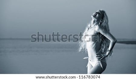 Beautiful young woman posing at the beach at sunset. Blue tone.