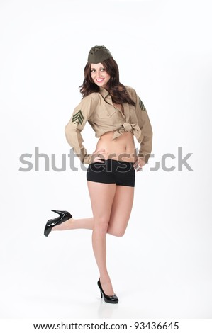 Beautiful young woman posing in black shorts, black heels and a military shirt and cap on a white background.