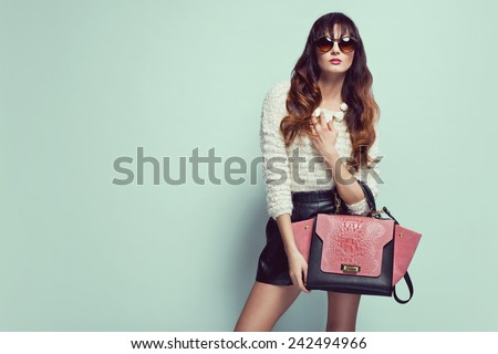 beautiful young woman posing in sunglasses, leather shorts, handbag and sweater