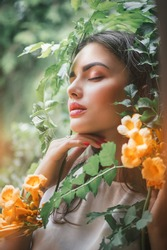 Beautiful young woman posing in Trumpet vine flowers in summer garden. Beauty model girl with Campsis. Enjoying nature outdoor.