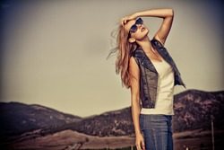 Beautiful young woman posing on a road over picturesque landscape.