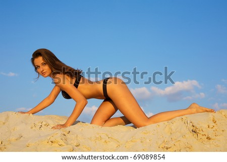 Beautiful young woman posing on sand