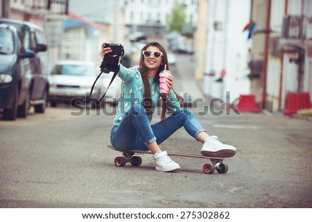 Beautiful young woman posing with a skateboard seat on skate street fashion lifestyle Keep cocktail and make selfie photo