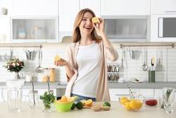 Beautiful young woman preparing lemonade in kitchen