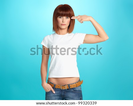 beautiful, young woman pretending to shoot a gun at her head, on blue background - stock photo