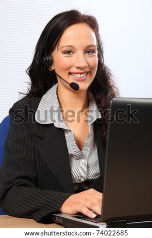 Beautiful young woman providing customer service with a smile, sitting to her computer speaking on a telephone headset. She is wearing a dark business suit.
