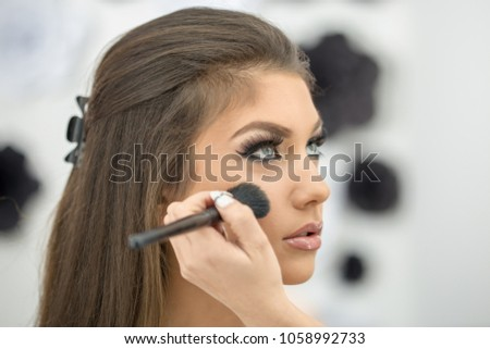 Beautiful young woman putting on make up in front of a mirror with a brush #1058992733