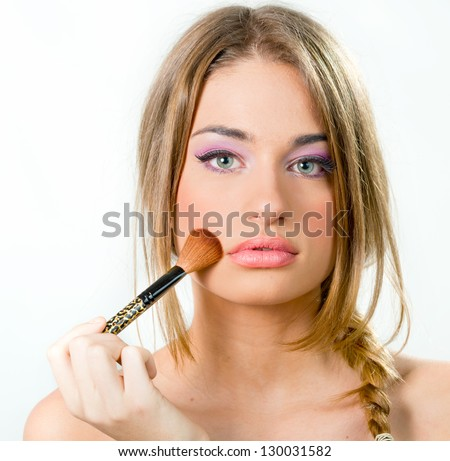 Beautiful young woman putting on makeup over a white background