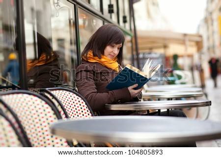 Beautiful young woman reading a book in cafe