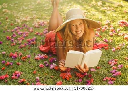 Beautiful Young Woman Reading a Book Outside on the Grass