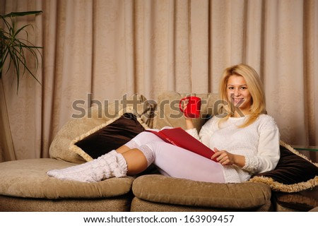 beautiful young woman reading a book while sitting on the couch