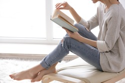 Beautiful young woman reading book near window at home
