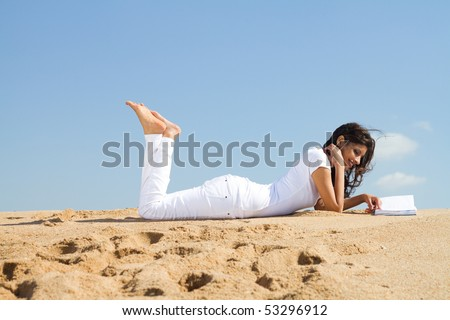 beautiful young woman reading book on beach - stock photo