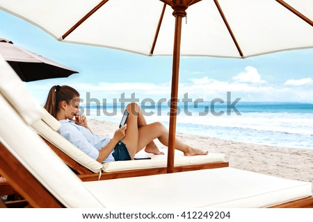 Beautiful Young Woman Reading E-book While Relaxing On Lounger Under Umbrella On Beach On Summer Holidays Vacations. Girl With Electronic Book Lying On Deck Chair Under Tent By Sea In Leisure Time