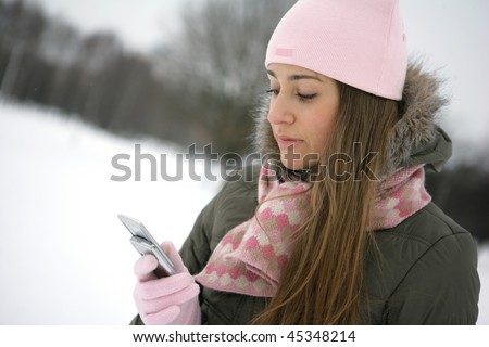 Beautiful young woman reading sms on her cellular phone
