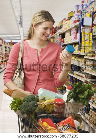 Beautiful young woman reads the label on a jar while shopping at a grocery store.  Vertical shot. - stock photo