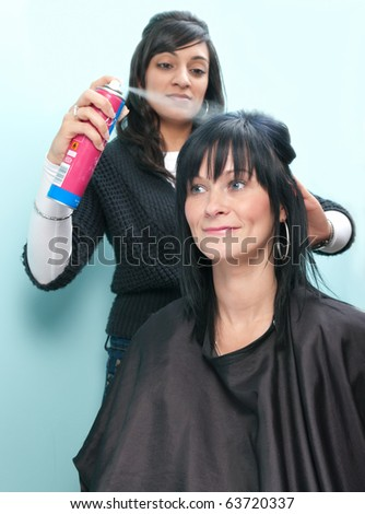Beautiful young woman receives hairspray from attractive Indian hair stylist