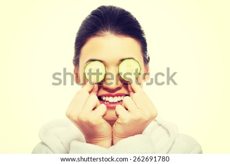 Beautiful young woman receiving facial mask of cucumber.