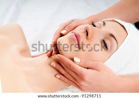 Beautiful young woman receiving facial massage with closed eyes in a spa center