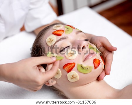 Beautiful young woman receiving fruit mask on a face in beauty salon - indoors