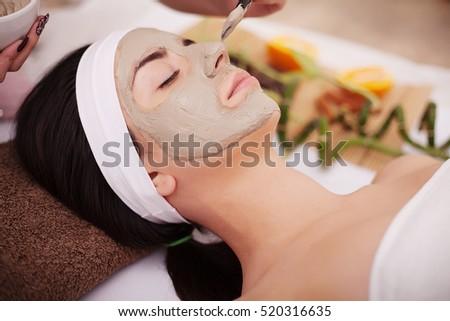 Beautiful young woman receiving gray facial mask in the beauty salon