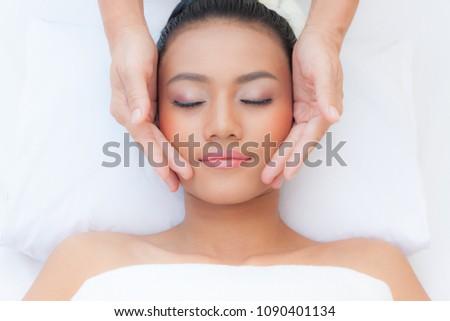 Beautiful young woman receiving massage in spa salon