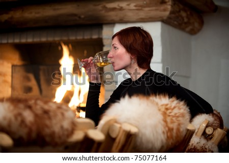 beautiful young woman relaxing and drinking wine in a cozy house with fireplace