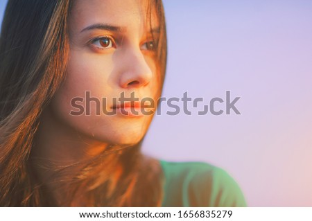 Beautiful young woman relaxing and enjoying sun at sunset. Beauty sunshine girl side profile portrait. Pretty happy lady enjoying summer outdoors. Positive emotion life success mind peace concept