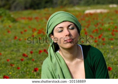 Beautiful young woman, relaxing in a pretty field of red flowers