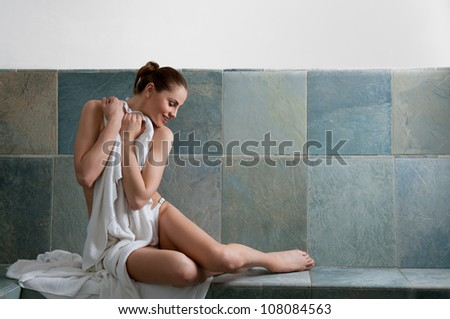 Beautiful young woman relaxing in a Turkish bath at spa - stock photo