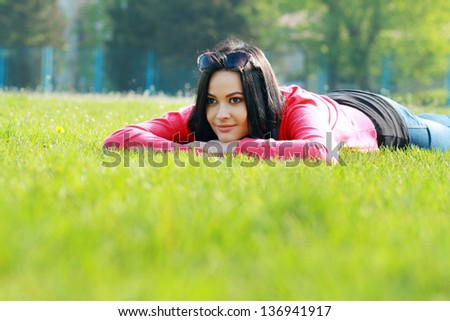 beautiful young woman relaxing in the grass in the city park