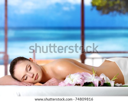 Beautiful young woman relaxing in the spa  salon in a resort - nature background