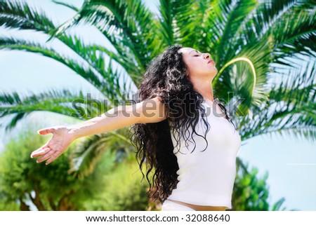 beautiful young woman relaxing in tropical setting