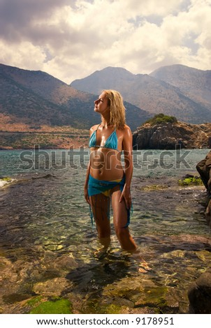 Beautiful young woman relaxing in water at sunset