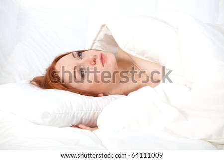 beautiful young woman relaxing in white bedding
