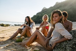 Beautiful young woman relaxing on the beach with her friends in background. Group of friends on beach holiday.