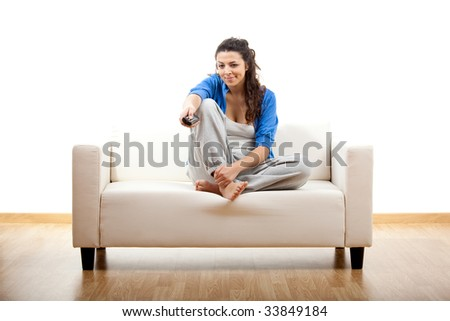 Beautiful young woman relaxing on the couch holding a remote control - isolated on white